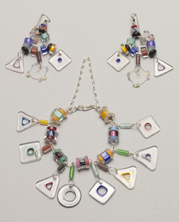 Each of clear and colored glass charms in geometric shapes linked to and hung from central silver loop.