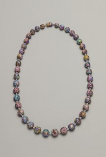 String of spherical beads decorated with faces and colorful patterns.