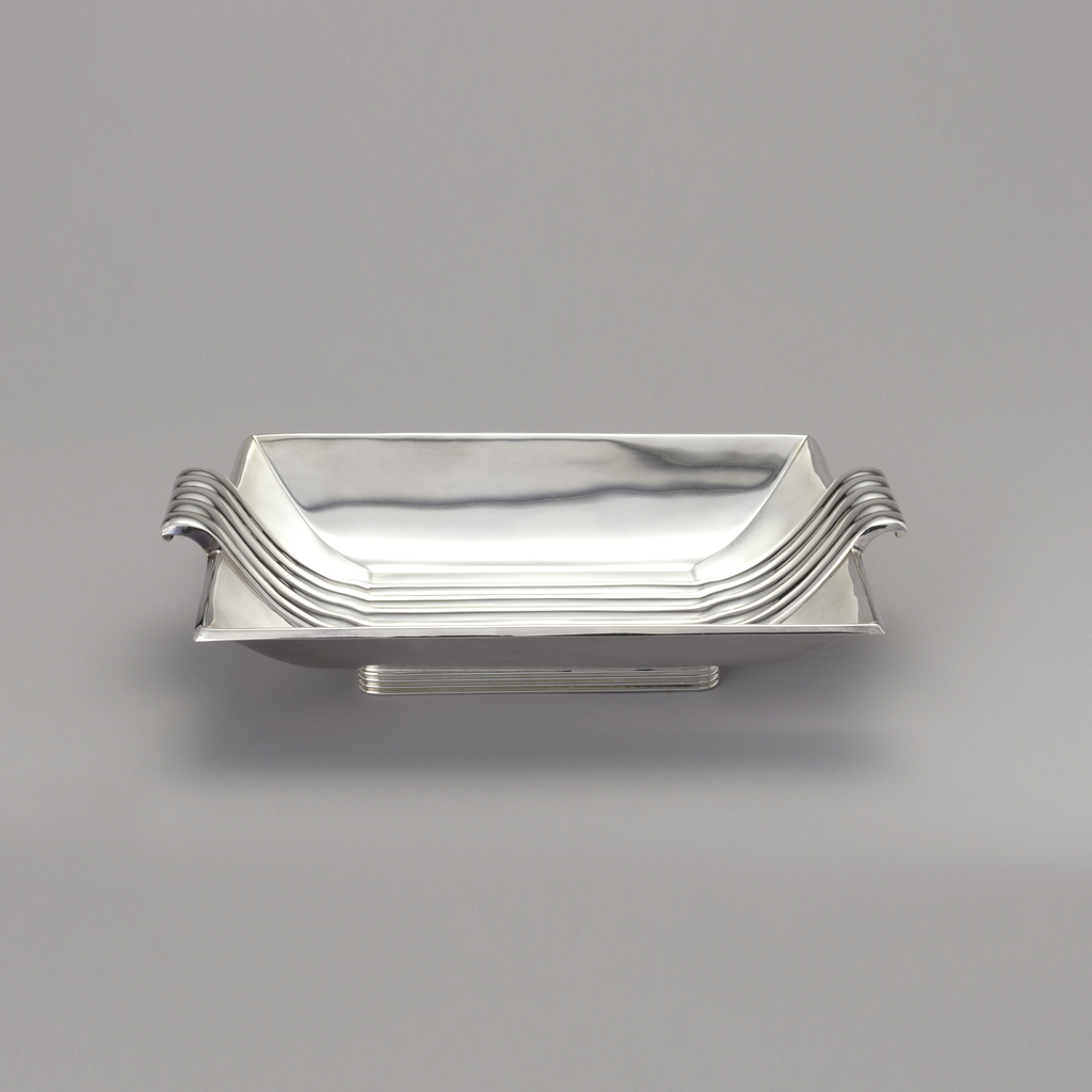Rectangular tray with curved sides, striated foot; decorative striations across interior of the tray which also reach out passed tray edges turning into handles.