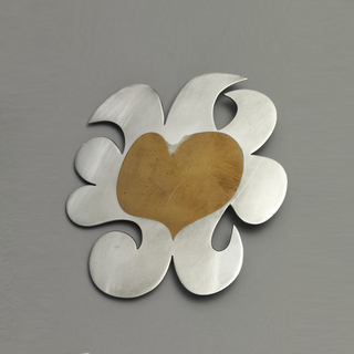 Brooch composed of a copper heart surrounded by silver curved border.