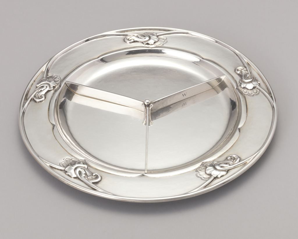 Circular plate, flat based, with plain concave center. Wide border chased with fine stylized blossoms and curled tendrils to create five lobes within rim. Around center, five lobes. Three-pronged divider.