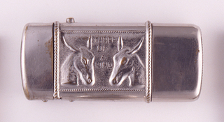 "Oblong, with rounded corners, featuring central, raised decoration of two donkey heads, each facing the other, between them is inscription ""Three Of A Kind"", all framed by twisted ropework. Plain case lid flips open at left of decoration by pressing small metal button on top, upper left.  At right is plain slip-off cover that conceals pair of miniature dice. Reverse features raised decoration of delicate arabesques surrounding a central, empty, oval reserve that is framed with ropework, all reverse ornament framed again with twisted ropework. Striker is on bottom of slip-off cover."