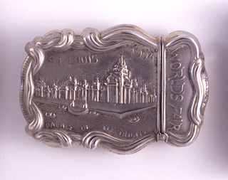 "Oblong, with ornate curved sides, cinched where lid meets box body, featuring raised horizontal decoration depicting large pavillion-like building, inscribed  ""St. Louis 1904"" above architectural rendering, and ""Palace of Electricity"" below. Inscribed on lid, and legible when box is turned long side up is ""World's Fair"", all decoration framed by winding, sinuous, fabric-like band that wraps around perimeter of box. Reverse features raised decoration of woman, seated in garden setting, dressed in long, Classical-style garment, drying her hair, probably based on figure of Venus, behind her is statue of a similar theme, all framed by c-curves and counter-curves. Lid hinged on upper, long side. Striker on bottom."