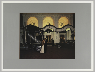 Photograph of hotel façade, a couple is embracing before a large black semi-truck. This is all framed by a gray border.