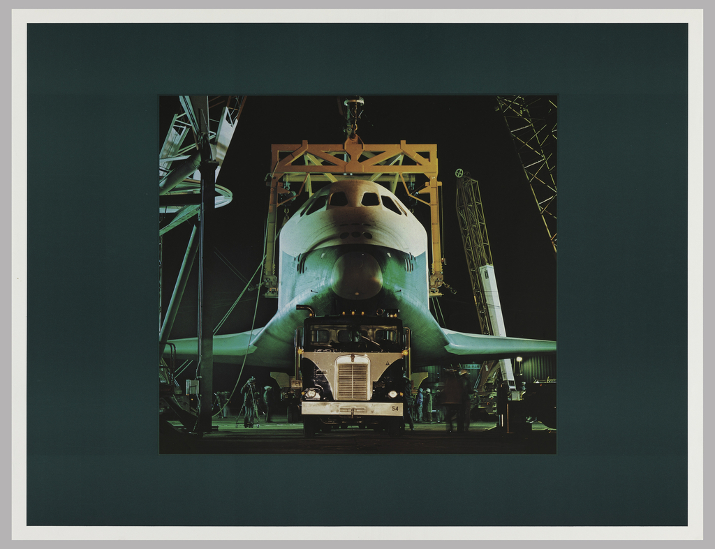 Photograph of the front of an airplane with a semi-truck in front of it; cranes around; all framed by a dark green border.