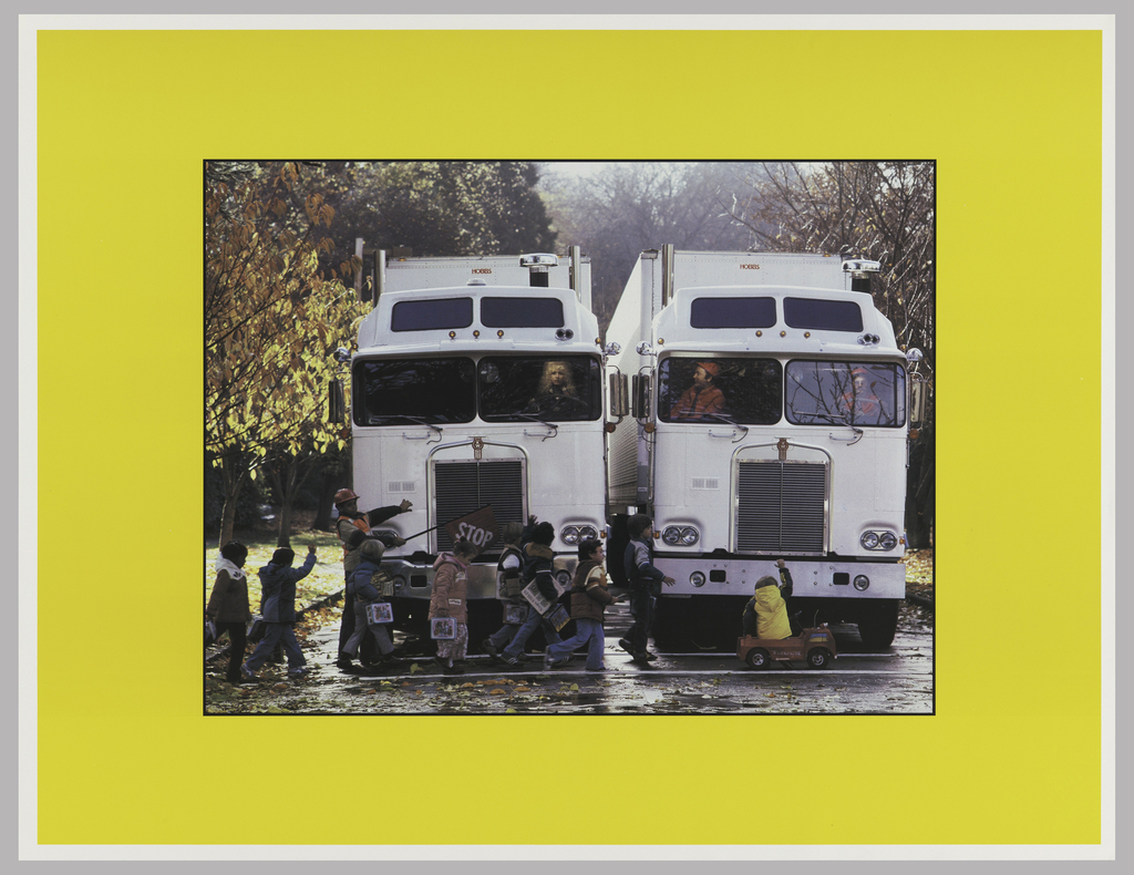 Photograph of the front of two white semi-trucks; the driver (male) of one looking into the cab of the other, at the blonde female driver; both stopping for a group a small children crossing the street; all framed by a yellow border.