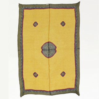 Yellow cotton panel of two strips stitched together in the center, with a border of black with yellow circles on a red stripe. In the center a lage medallion in black with white circles and a red border. In each corner are smaller medallions of the same coloration.