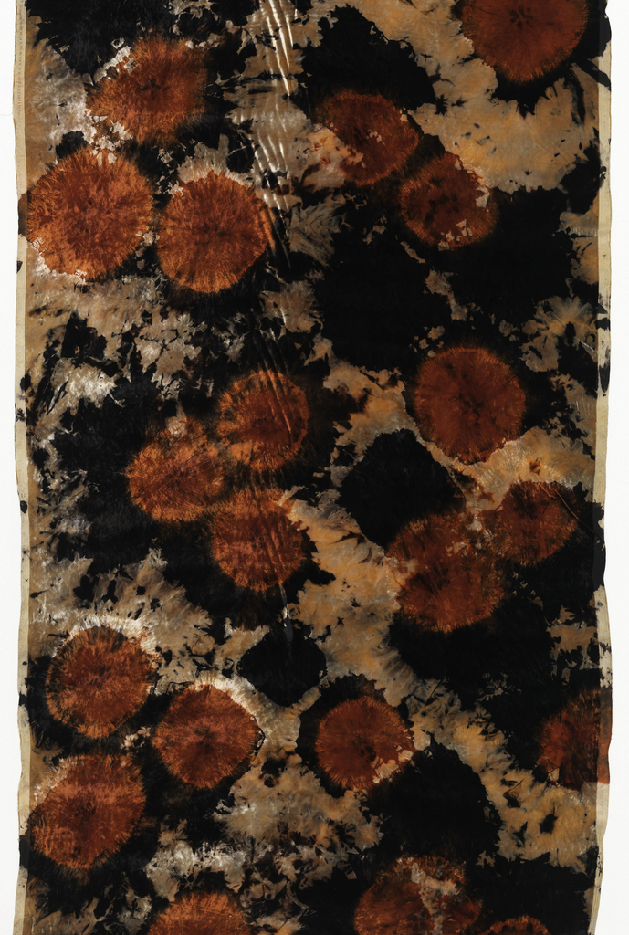 Length of tied, dyed and bleached velvet in an allover pattern of red circles on top of black circles or black circular-like splashes on a light gray-orange background. The light background is achieved by bleaching.