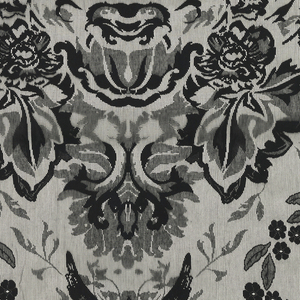 """Black lace with a vertically symmetrical """"urn and flowers"""" style pattern, where the urn is replaced by the face of the devil, and the cherubs by tiny demons."""