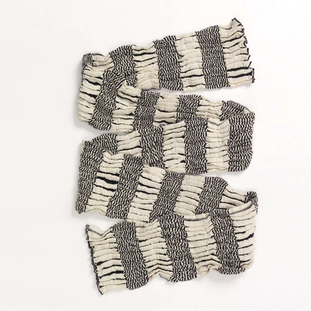 Double cloth of thick and thin stripes in black and white. Vertical bands of thick black and white stripes alternate with horizontal bands of thin black and white stripes. Overtwisted black threads create a puckered effect.