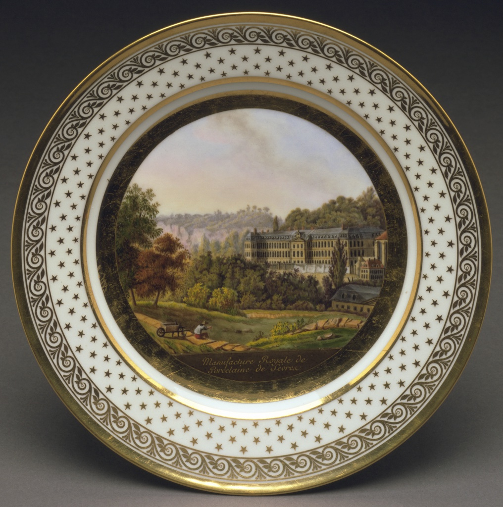 Flat marli.  Concentric bands, in gold: plain, advancing wave motif, and scattered stars; enclosing view of the Sèvres porcelain factory in colors after an 1817 drawing by Achille Etna Michallon.