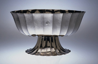 A fluted oval raised silver fruit bowl with matte finish, engraved with a monogram on the sides, all on a raised fluted oval foot that splays out from the bowl.