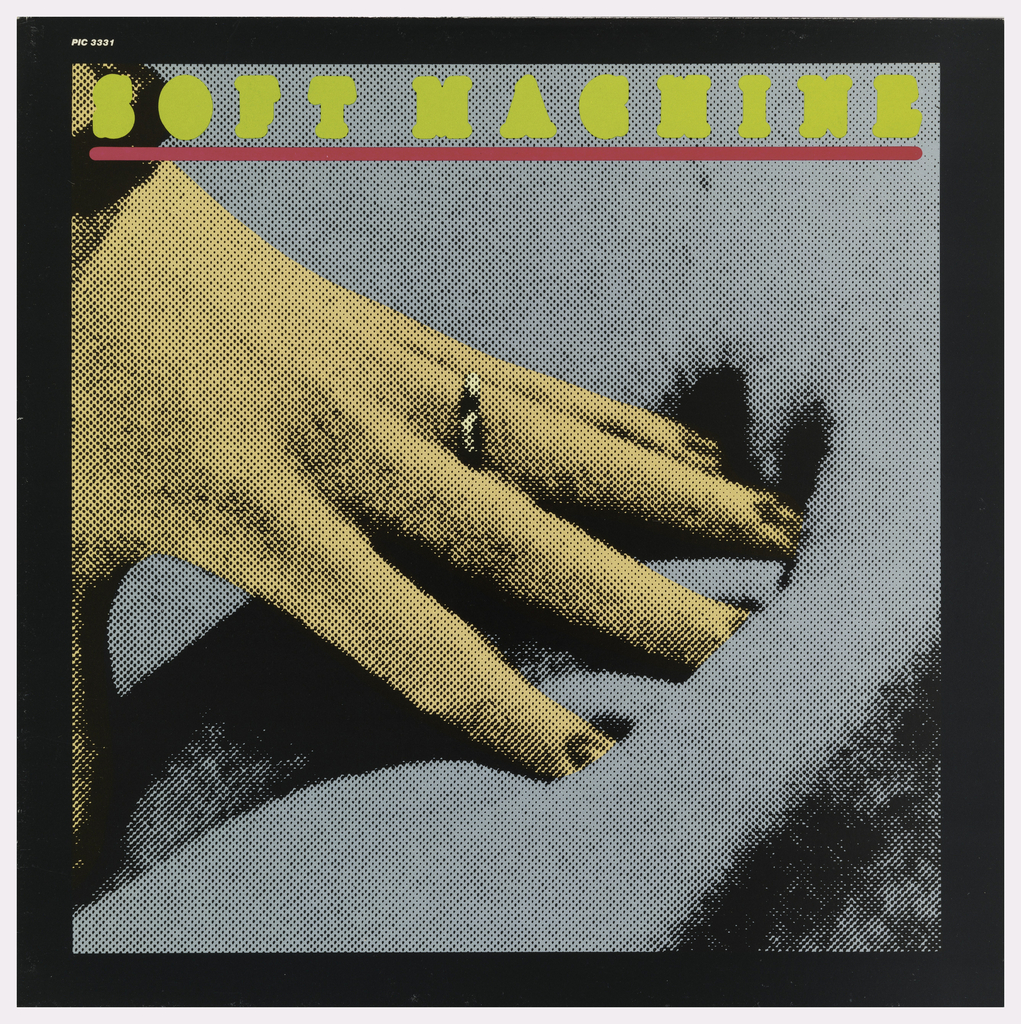 Image of a woman's hand pushing into or resting on a soft cushion or fabric. Above in yellow: SOFT MACHINE.