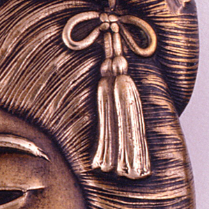 In the form of a Geisha's head in 3/4 profile, with raised, finely rendered ceremonial hairdo that wraps from front to back, featuring assortment of hair ornaments, including a large flower with bow and tassles on front, textured comb on reverse. Lid opening intersects upper part of hairdo, hinged on right side. Striker located on lower right, at base of neck.