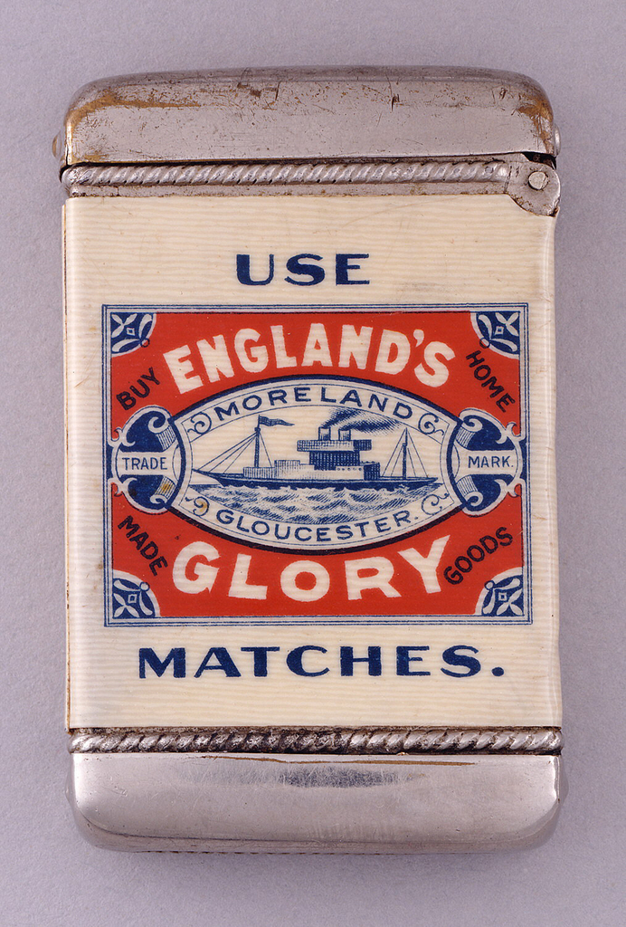 "Rectangular, with rounded corners, featuring printed advertisement for S.J. Moreland & Sons. The front displays red, white and blue rectangular reserve with freighter boat illustrated in oval at its center, inscribed ""England's Glory,"" ""Buy Home Made Goods,"" ""Moreland Gloucester,"" ""Trade Mark""; ""Use Matches"" inscribed in blue outside rectangle. Inscribed in blue on reverse, ""Compliments of S.J. Moreland & Sons, Gloucester. Manufacturers of Safety & Paraffin Matches, Also Wax Vestas."" Lid hinged on side. Striker in recessed groove on bottom."