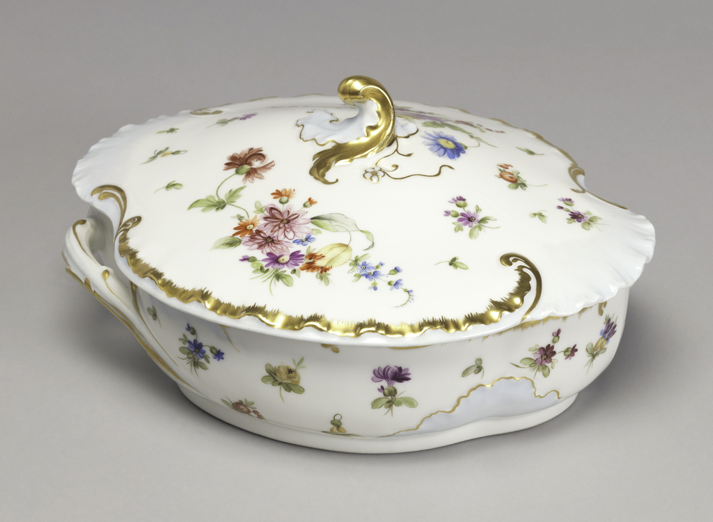 a) Assymetrically-shaped white porcelain vegetable dish with two handles and b) cover with gilt curved finial. Both are decorated with floral sprays and strewn flowers, rippled and gilt rococo borders and pale blue areas.