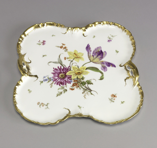 Quatrefoil-shaped tray of white porcelain with four equal lobes and two assymetrical, gilt, leaf-form handles; gilt, rippled rim; in center, floral spray, small flowers scattered on background.
