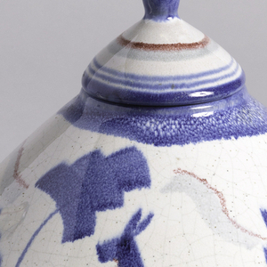 Circular teapot, widest in the middle.  Spout rises from the middle at approximately a twenty degree angle and sits across from the curved handle.  White background with surface decoration of blue, rose, and gray lines and stylized blue deer and trees.  Conical lid decorated with lines of blue, gray, and rose and a round blue finial.