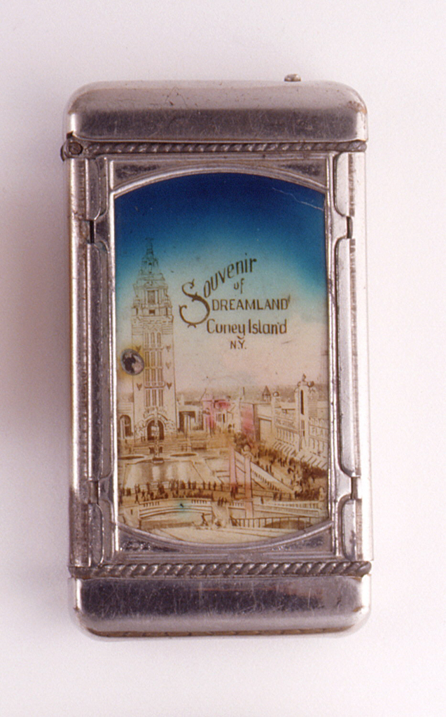"""Rectangular, featuring smaller rectangular panel insert with colored image of amusement park, inscribed """"Souvenir of Dreamland, Coney Island, N.Y."""", reverse features rectangular panel insert with colored image, inscribed """"Chutes and Lake Dreamland, Coney Island"""". Lid hinged on side. Striker on bottom."""