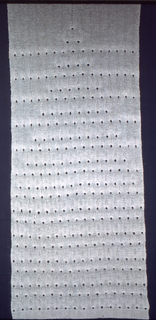 Vertical rectangular hanging knitted in white linen with an overall triangular design formed of rows of 3/4 inch holes.