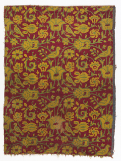Silk velvet textile showing pattern of green and yellow arabesques with flowers and birds on a red ground. Right selvage present.