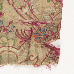 Two fragments of a continuous pattern in the bizarre style placed side by side. Ground in shades of gold with floral design in red, green, yellow and blue. Each fragment has one selvage present.