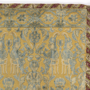 Velvet panel bound on four sides with a striped floral patterned silk. The velvet is patterned with rows of men standing, seated cross-legged, and confronted seated on chairs with birds, in a garden. In light blue and ivory pile on a pale yellow pile foundation.