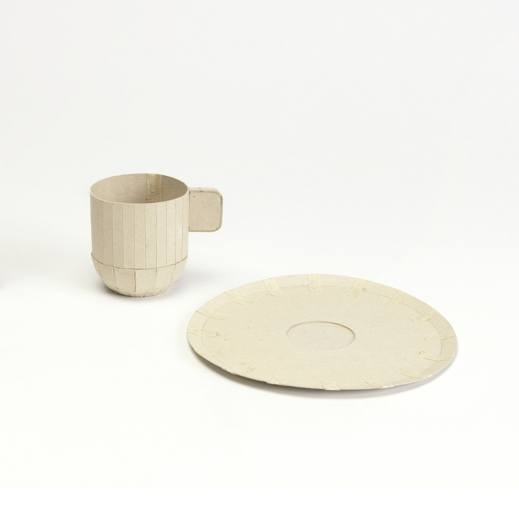 Circular saucer with narrow upturned rim and impression for cup. Cut and scored light gray cardboard; 16 applied paper tape marks from edge towards center