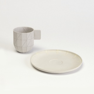 "Slip cast cylindrical cup with straight sides, squared D-shaped tab handle and curved tapered base. Light gray, unglazed porcelain; grid-like pattern formed from regularly-spaced vertical scores divided by two horizontal scores; randomized diagonal scores cut across grid, all with applied pencil. ""S&B / 2009 / 2"" mark applied to underside in marker or ink"
