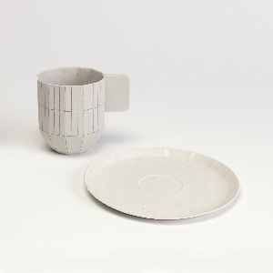 "Slip cast circular saucer with slightly upturned rim and impression for cup. Light gray, unglazed porcelain; 16 applied lines at regularly-spaced intervals from edge towards center with cream-colored glaze. ""S&B / 2009 / 2"" mark applied to underside in marker or ink"