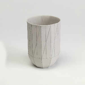 """Slip cast cylindrical cup with tall straight sides and curved tapered base. Light gray, unglazed porcelain; regularly-spaced vertical scores with diagonal scores, terminating at a horizontal score towards base; broader vertical scores at curved base, all with applied pencil. """"S&B / 2009 / 2"""" mark applied to underside in marker or ink"""
