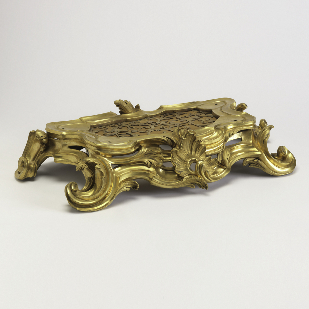 formed of a series of S-curves in ormolu, surrounding a grille on the top with curvy scroll decoration, the front and back of different scroll forms, the front with central asymmetrical shell