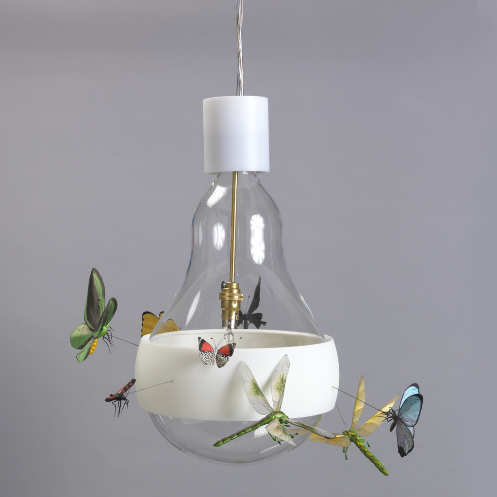 Hanging lamp in the form of a large clear glass incandescent light bulb, the globe surrounded by a transluscent white plastic band from which project eight colorful, realistic figures of winged insects seemingly in flight around the bulb; halogen light source suspended from brass fitting in center of bulb-shaped globe.
