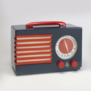 Blue rectangular case with long red horizontal handle on top; face with red and white horizontally striped grill on left, circular red and white station selection dial above two red circular control knobs on right; each control knob with molded decoration of five-pointed star.