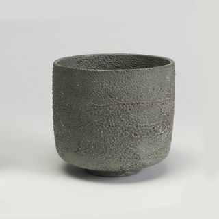 Short cylindrical form on foot ring; mottled glaze of thick pebble-like and bubbled matt gray over pale green.