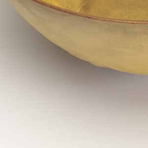Circular form with tapering sides on high foot ring; matte yellow glaze unevenly applied.