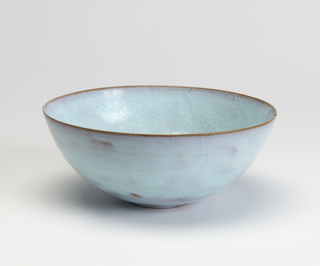 Hemispherical form on low foot; robbin's egg blue-to-purple glaze, brown edge at rim.