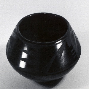 The coil-built bowl rests upon a flat foot; the body tapers outward to an angled low shoulder and in at an angle toward the lip. The shoulder area is decorated with a running band of geometric motifs burnished against a matte ground. The lower body is entirely burnished as is the lip.