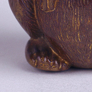 In the form of a seated monkey, with arms folded at his front and right thumb touching his mouth, features and fur highlighted by brass and reddish-brown patinated finish, glass eyes. Head, which serves as lid, hinged on back. Link attached on his upper right arm. Striker in recessed groove on bottom, beneath his feet. Box may sit upright on table.