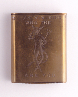 """Rectangular, rounded sides, featuring word/picture rebus, inscribed """"I Am W.W. King, Who The [Devil] Are You"""", with incised image of devil with pitchfork that appears after """"The"""" and before """"Are"""" in text. Reverse inscribed with monogram WWK. Thin, flat lid hinged on upper left. Striker on bottom."""