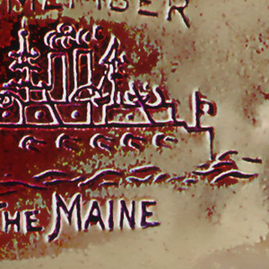 """Oblong, rounded corners, with horizontal image of the battleship Maine, above which is inscribed """"Remember"""" and below """"The Maine."""" On reverse is image of the American flag. Lid hinged on left. Striker on bottom."""