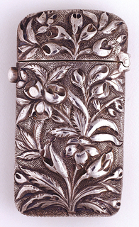 """Oblong, rounded sides and corners, featuring over-all repoussé floral decoration on stippled ground; reverse features some variation in floral decoration with monogram """"EM"""" engraved in small, open, central reserve. Small protruding button on side opens lid when depressed; lid hinged on opposite side. Striker on bottom."""