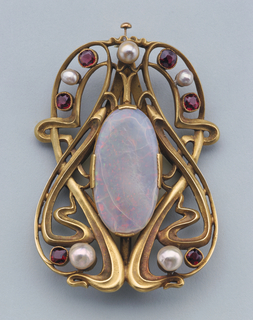 A gold and abstract buckle with a large oval opal in the middle and accented with small opals, pearls, and garnets around the sides.