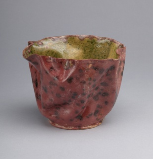 Buff-colored clay body, thrown. Free-formed body, variously crumpled and folded with slightly ruffled rim; low flat foot. Variegated rose and pink glaze with dark brown splotches covering exterior. Glaze has a certain white opaqueness with various burst bubbles on surface, thick at base. Interior is glazed a light yellow-green with mottled green specks. Kiln stilt marks on interior of bowl, near bottom.