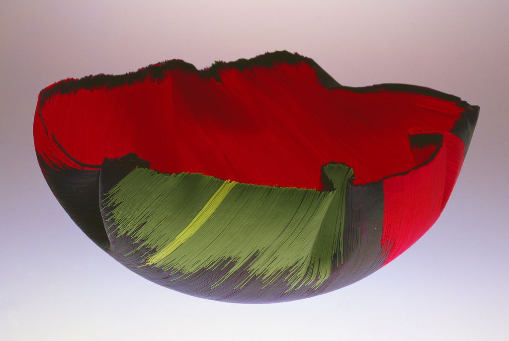 Hemispherical bowl formed of layered glass threads in iridescent black, scarlet, pale and medium green, mauve. Individual threads pulled and slumped into form, edges manipulated to create irregular edge folds and indentations.  Interior layered with red; exterior primarily black with green and mauve passages at opposite edges.
