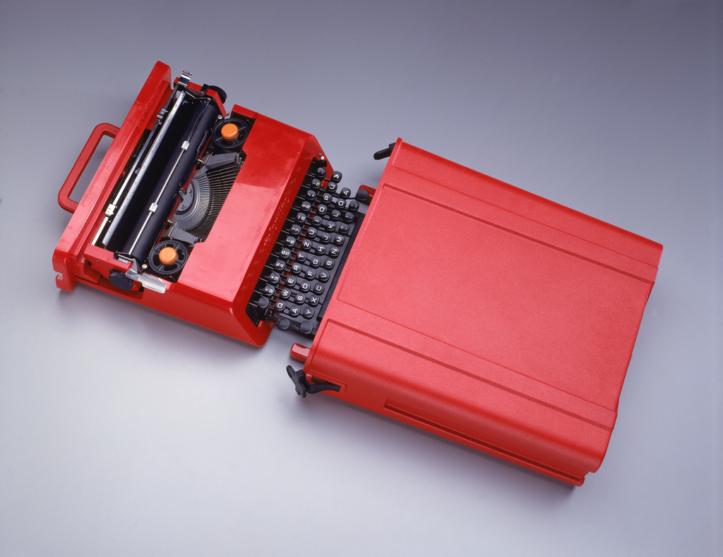 Red plastic rectangular typewriter (a); open keyboard with standard alphabet on black keys; two ribbon spools, each with orange button in center; red handle on back. Contoured, rectangular matte red plastic case (b), open on one side, into which typewriter slides; black rubber tab on each side of opening that attach to and secure typewriter.