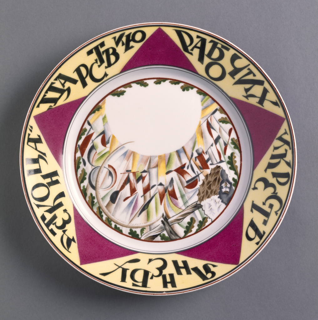 """Circular; with red star and the inscription, in Russian, """"The reign of workers and peasants will be without end"""" around gilt overglaze rim border; in the center a white partial orb, a hammer and sickle, and the inscription, in Russian, """"Commune."""""""