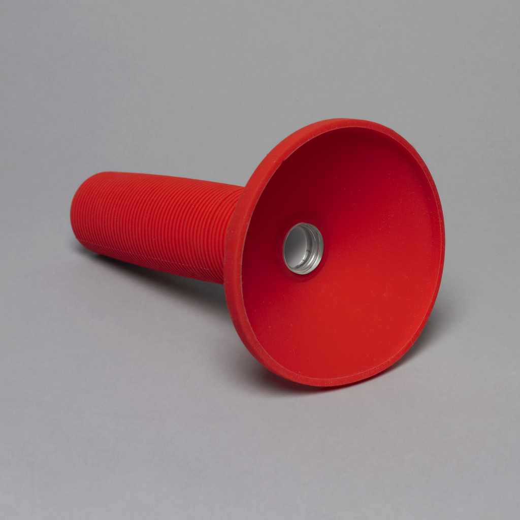 Red silicone rubber body comprising long cylindrical handle with horizontal striations and broad cylindrical suction-cup like lamp with small circular lens in center, covering LED light source.