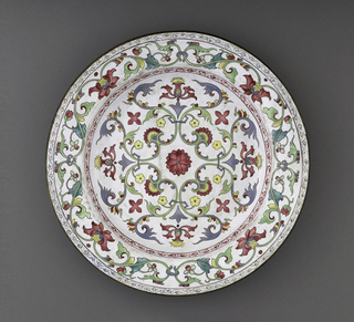Circular plate with symmetrical, polychrome floral and scroll work decoration on white ground.