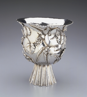 A silver vase with a pattern of leaves around the sides. This vase also has a carved and raised foot, and a flared lip.